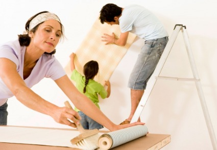 Family working on home improvements- wallpapering