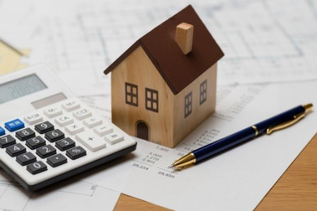Image of small wooden house, pen and calculator on financial paperwork