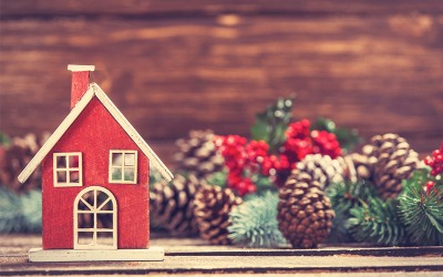 Image of small red wooden home surrounded by holiday greens, pine cones and holly berries.